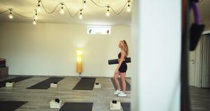 Junge Dame des Wellnessyogastudios, die in das Studio kommt, ihre Yogasitzung zu beginnen sie, ihre eigene Sportmatte mit a zu ha stock video footage