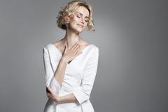 Junge Dame des Zaubers, die modisches weißes Kleid trägt Stockbild