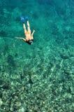 Junge Dame, die über Korallenriffen schnorchelt Stockfotografie