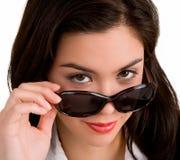 Junge Dame, die über Sonnenbrillen schaut Lizenzfreie Stockfotografie