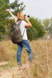 Junge Dame, die auf eine Landstraße mit Digitalkamera geht Stockfoto