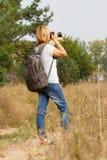 Junge Dame, die auf eine Landstraße mit Digitalkamera geht Stockbilder