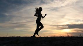 Junge Dame, die auf Küste bei Sonnenuntergang läuft stock video footage
