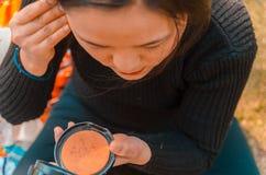 Junge Dame, die auf sie sich setzt, bilden das Schauen auf einem Taschenspiegel lizenzfreies stockfoto