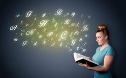 Junge Dame, die Buch mit Buchstaben hält Stockfotos