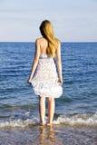 Junge Dame, die in den Seewellen steht Lizenzfreies Stockfoto