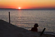 Junge Dame, die den Sonnenuntergang überwacht Lizenzfreie Stockbilder
