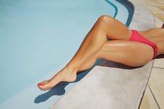Junge Dame, die durch Swimmingpool sich entspannt Stockbilder