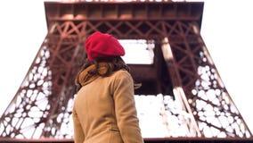 Junge Dame, die Eiffelturm, Sightseeing-Tour während der Ferien in Paris betrachtet stockfotografie