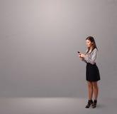 Junge Dame, die ein Telefon mit Exemplarplatz steht und anhält Lizenzfreies Stockfoto