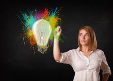 Junge Dame, die eine bunte Glühlampe mit buntem zeichnet, spritzt Lizenzfreie Stockfotos