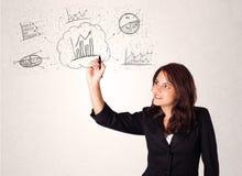 Junge Dame, die Finanzdiagrammikonen und -symbole skizziert Lizenzfreies Stockbild