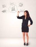 Junge Dame, die Finanzdiagrammikonen und -symbole skizziert Lizenzfreie Stockbilder