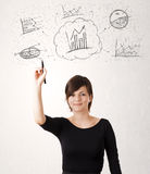 Junge Dame, die Finanzdiagrammikonen und -symbole skizziert Stockfotografie