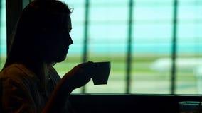 Junge Dame, die am Flughafenrestaurant sitzt und heißen Kaffee, Tourismus genießt lizenzfreie stockfotografie