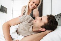 Junge Dame, die ihren Ehemann beim Lügen im Bett betrachtet Lizenzfreies Stockbild