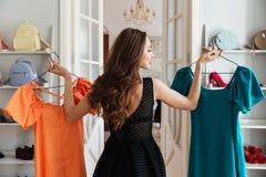 Junge Dame, die im Kleidungsshop wählt Kleider steht Lizenzfreie Stockbilder