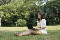 Junge Dame, die Laptop auf Gras verwendet Stockbilder