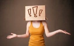Junge Dame, die mit einer Pappschachtel auf ihrem Kopf mit excla gestikuliert Stockfotografie