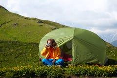 Junge Dame, die nahe einem Zelt vor schneebedeckten Bergspitzen sitzt Lizenzfreie Stockbilder