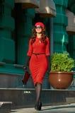 Junge Dame, die in rotes Kleid in der Stadt geht Stockfotografie