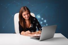 Junge Dame, die am Schreibtisch sitzt und auf Laptop mit Sozialnetw schreibt Lizenzfreie Stockfotos