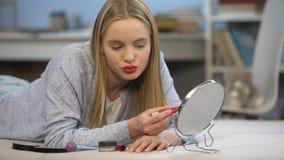 Junge Dame, die am Spiegel, Flirtpraxis blinzelt, möchte Mannaufmerksamkeit erregen stock footage