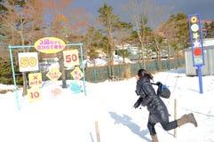 Junge Dame, die Spiel auf dem Schnee spielt Stockfotografie