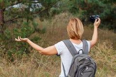 Junge Dame, die an am Wald mit Digitalkamera geht Lizenzfreies Stockbild