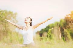 Junge Dame, die Yogaübung Bereich des grünen Feldes im im Freien zeigt die Ruhe ruhig im Meditationsverstand tut stockfotografie