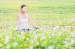 Junge Dame, die Yogaübung Bereich des grünen Feldes im im Freien zeigt die Ruhe ruhig im Meditationsverstand tut lizenzfreie stockbilder