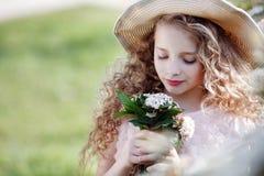 Junge Dame in einem Strohhut auf einem Frühlingsrasen unter blühenden Büschen lizenzfreies stockfoto