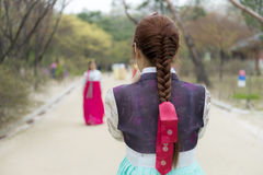 Junge Dame flocht das Haar in traditionellem koreanischem hanbok Kostüm, das ein handphone geschossen auf Park nimmt Stockbild