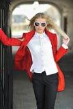 Junge Dame im roten Kleid, das draußen tragende Sonnenbrille aufwirft Stockbild