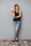 Junge Dame mit der Tasse Kaffee-Aufstellung lokalisiert Lizenzfreie Stockfotos