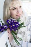 Junge Dame mit einem Blumenstrauß der Iris und der Tulpen, die das spri genießen Lizenzfreie Stockfotos