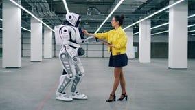 Junge Dame reguliert Einstellungen eines menschlich ähnlichen Roboters stock video