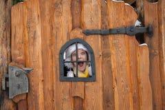 Junge Dame schaut durch ein hölzernes Tor Stockfotografie