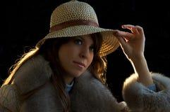 Junge Dame tryimg auf einem Hut Lizenzfreies Stockfoto