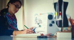 Junge Damenschneiderin, die Kleidungsmuster auf Papier entwirft stockbild