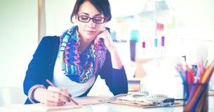 Junge Damenschneiderin, die Kleidungsmuster auf Papier entwirft stockfoto