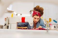 Junge Damenschneiderin, die zufällige Kleidung bei der Anwendung ihrer Nähmaschine bei der Arbeit trägt lizenzfreie stockfotografie