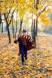 Junge in den Gläsern läuft in Herbstpark mit Goldblättern, hält Buch in seinen Händen lizenzfreie stockfotografie