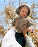 Junge in den Händen des Vaters Lizenzfreies Stockbild