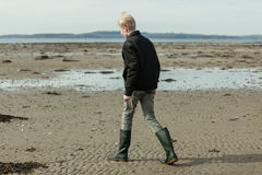 Junge in den hohen Stiefeln und Jacke, die auf Strand gehen Lizenzfreie Stockbilder