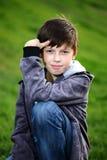 Junge in den Jeans sitzt auf einem Gras Lizenzfreie Stockbilder