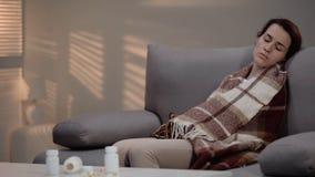 Junge deprimierte Dame, die auf Couch liegt, nachdem zu viel Pillen, Selbstmordversuch genommen worden sind stockfoto