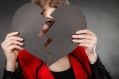 Junge deprimierte Frau abgedeckt durch defektes Herz Stockbild