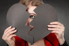 Junge deprimierte Frau abgedeckt durch defektes Herz Stockbilder