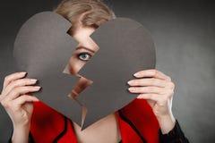 Junge deprimierte Frau abgedeckt durch defektes Herz Stockfoto